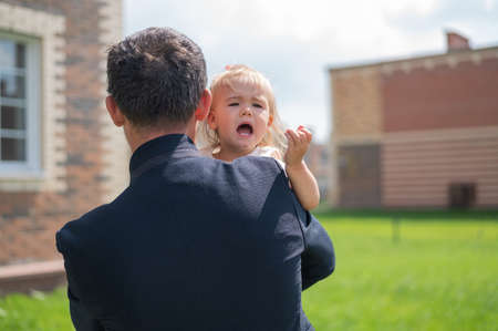 Caring father holds on hands of his little daughter outdoors.