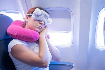 Tired red-haired woman sleeping on the plane with an eye mask and a neck pillow