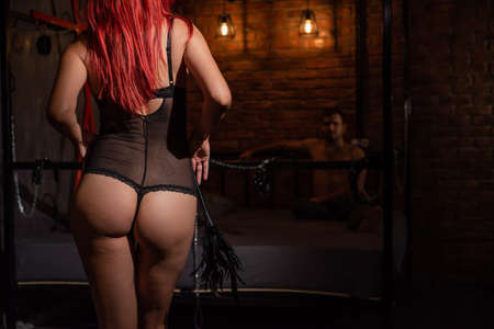 A redhead woman with a beautiful booty in black underwear stands with a whip and dominates the man during sexual games