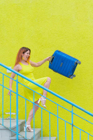 Happy red-haired woman in a yellow dress goes upstairs holding a blue suitcase.