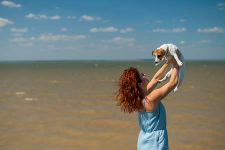 Happy woman hugs with a dog by the sea. Red-haired Caucasian girl holding a Jack Russell Terrier puppy. Love between pet and owner.