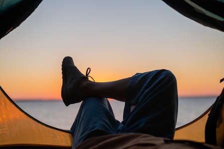 View of female legs in a tourist tent at sunset on the beach. The woman is hiking and camped on the riverbank. 版權商用圖片