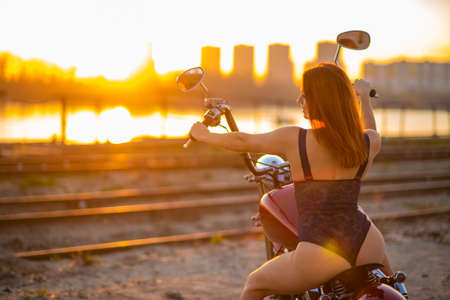 Red-haired woman in lingerie in high heels sits on a motorcycle. Attractive red-haired girl sits on a motorcycle at sunset