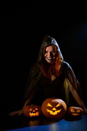 A creepy sorceress in a cloak casts a spell on pumpkins for Halloween