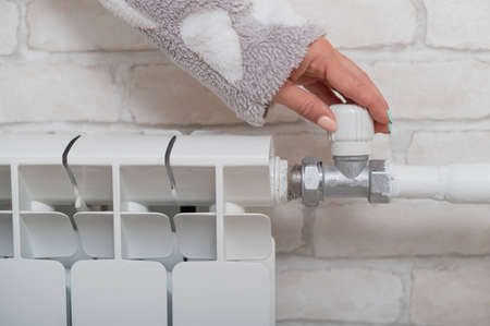 The woman opens the valve of the radiator heating.