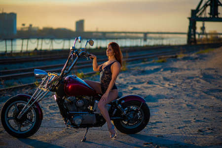 Red-haired woman in lingerie in high heels sits on a motorcycle