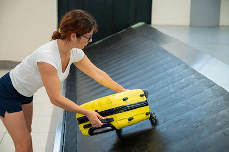 Caucasian woman picks up her yellow suitcase from the luggage belt at the airport terminal. Imagens