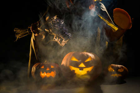 Witch casts a spell on a steaming pumpkin in the dark on Halloween Imagens