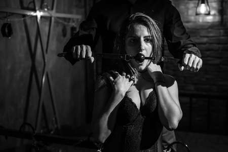 A man dominates and puts a gag in his partner mouth. BDSM concept. Portrait of a woman in seductive underwear with an intimate toy in her mouth. Sexy couple plays love games.