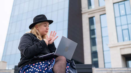Young woman speaks sign language on a video call on a laptop outdoors. The deaf-mute girl communicates with gestures