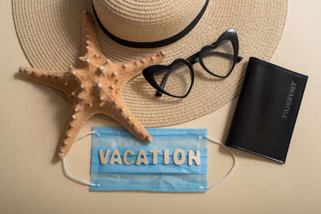 Straw hat sunglasses in the shape of a heart, passport, starfish and mask with the inscription vacation. Vacation concept at sea during a pandemic