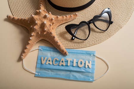 Top view of straw hat sunglasses starfish and mask with lettering vacation. Travel concept during the spread of coronavirus