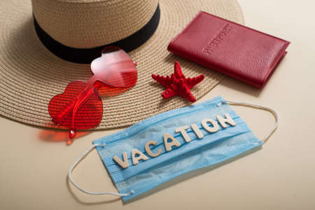Top view on hat sunglasses passport starfish and mask with inscription Vacation. Travel concept during the spread of coronavirus