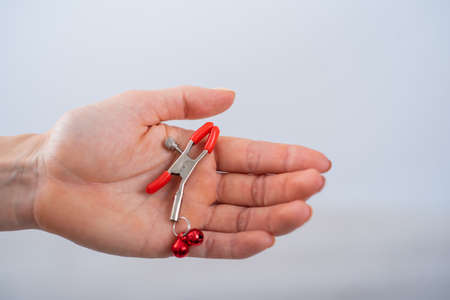 Close up nipple clamps in a female hand on a white background. BDSM sex toy