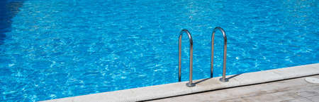 Close up grab bars ladder in the blue swimming pool outdoors