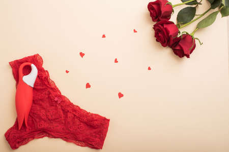 Flat lay. Womens red lace panties clitoral in the shape of a tulip and scarlet roses. The best gift for a woman for any occasion