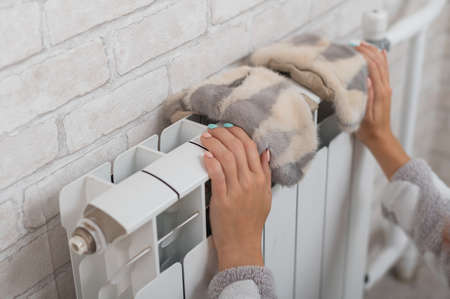 A woman hangs fur mittens on a radiator. Central heating on a cold winter day