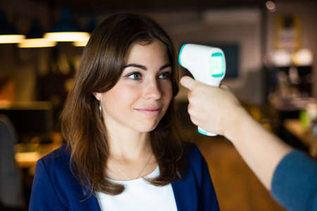 A faceless office worker checks a womans fever with an infrared thermometer in the office Banque d'images