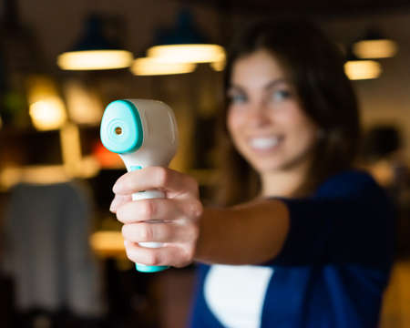 Beautiful smiling woman measures body temperature with infrared thermometer in the office