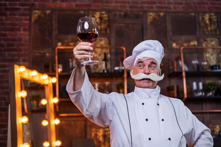 An elderly male chef degustation red wine in the kitchen