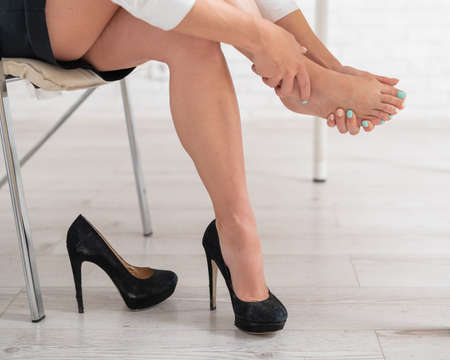 Business woman took off her black high-heeled shoes and massages her feet. Ankle pain from uncomfortable shoes