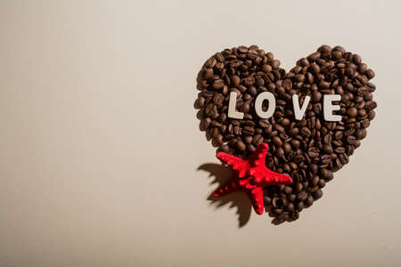 Top view of coffee grains in the shape of heart lettering love and red starfish