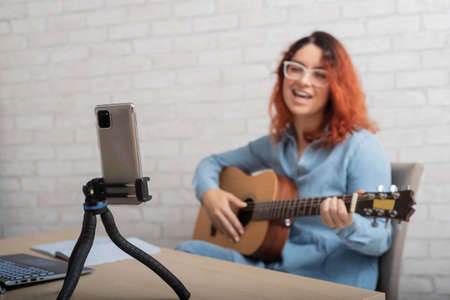 A woman is broadcasting online on her phone at home. The girl sings and plays the guitar live
