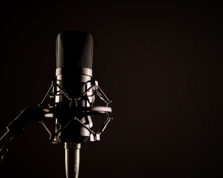 Close-up of a professional microphone for a radio broadcast on a black background. Recording studio equipment
