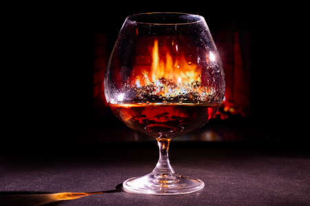 Close-up on a glass of brandy in the dark on the background of the fireplace 免版税图像