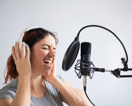 A woman with headphones is recording a song in a recording studio. Emotional girl sings with pleasure