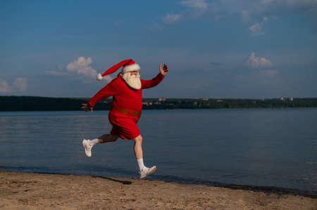 Santa Claus in shorts runs along the beach. Concept of celebrating christmas at sea