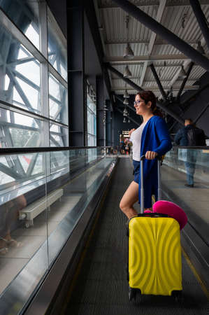 Caucasian woman on a horizontal escalator with a suitcase at the airport. A girl with pink luggage rides on a moving sidewalk Reklamní fotografie