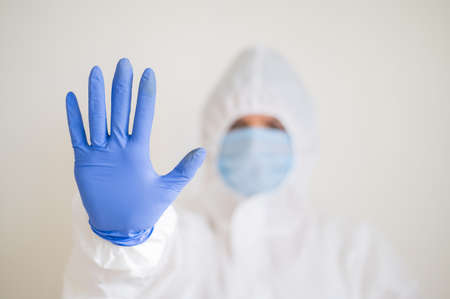 Woman in protective suit, medical mask and latex gloves, shows stop gesture. Tired doctor in the coronavirus epidemic