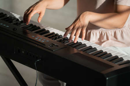 Close-up of female hands on the electric piano. Woman musician plays a keyboard instrument. Zdjęcie Seryjne