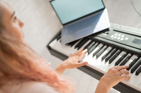 A woman watches video lessons on a digital tablet and plays on an electro synthesizer. The girl learns to play the piano remotely. Zdjęcie Seryjne