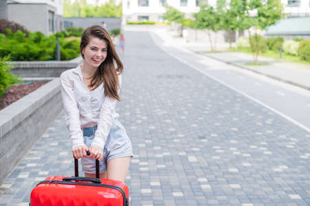A beautiful caucasian woman is walking down the street with a large luggage on wheels. The girl goes on vacation