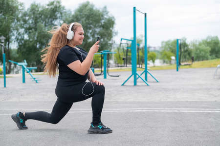 Fat young woman doing fitness exercises and listening to music from a smartphone outdoors