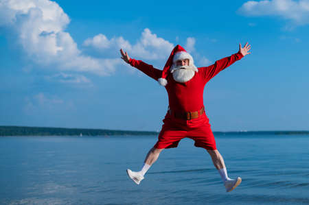 Santa claus in shorts is jumping on the beach. Concept of celebrating christmas at sea