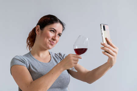 Caucasian woman drinks red wine and communicates with friends via video communication on a smartphone. The quarantined girl celebrates the holiday via an online conference
