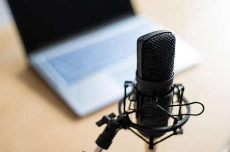 Close-up of a professional microphone on the background of a laptop. Radio broadcasters desktop