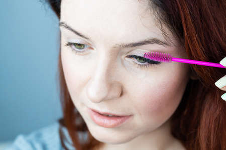 Red head woman brushing her extension eyelashes with a brush. girl with impending eyelid make-up mascara. Beauty industry. Stok Fotoğraf