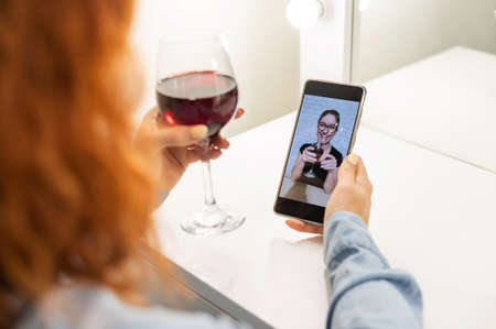 The women talk over video communication on the phone and drink red wine. The quarantined girl is not making a video call