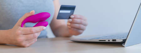 A faceless woman holds a credit card and a clitoral vibrator while sitting at a laptop. Online sex industry