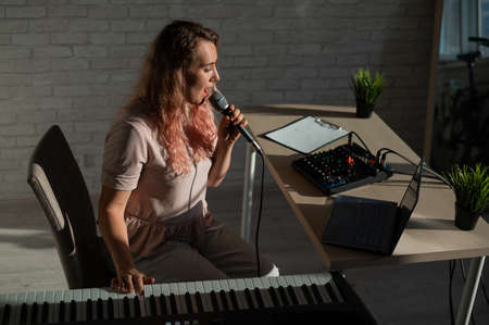 Expressive female singer has a video blog on a laptop. Portrait of a girl recording a song on a web camera and composing on a synthesizer. Online music lessons. Distance learning in quarantine.