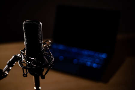 Close-up of a professional microphone on the background of a laptop in the dark Stock Photo