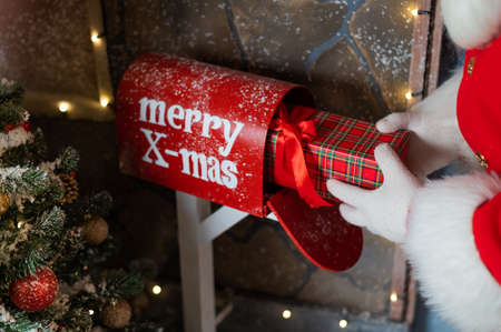 Close-up of hands of santa claus puts a gift in a mailbox. Christmas miracle