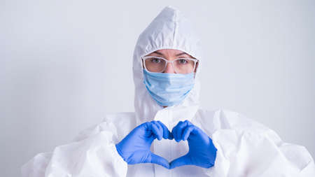 Female doctor in a protective suit shows the heart with a gesture. Patient health care concept 版權商用圖片