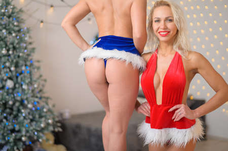Seductive female ass on the background of the Christmas tree. Two women bodybuilders posing in Santa Claus costumes at Christmas. Girl with big silicone breasts.