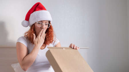 An excited red-haired woman in a Santa Claus hat sits in bed and opening a box with an order. Online shopping concept