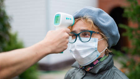 A doctor measures the temperature of an elderly woman wearing a mask with a non-contact infrared thermometer outdoors